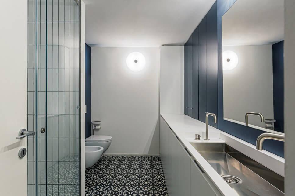 Großes Modernes Duschbad mit Kassettenfronten, weißen Schränken, offener Dusche, Wandtoilette, weißen Fliesen, Porzellanfliesen, blauer Wandfarbe, Zementfliesen, Unterbauwaschbecken, blauem Boden und weißer Waschtischplatte in Mailand