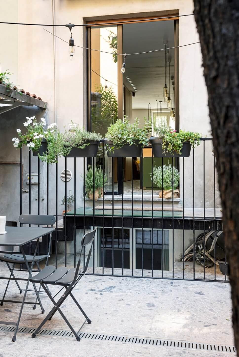 Begrünter Innenhof mit Gartentisch und Klappstühlen vor einem Balkon mit Blick in eine Wohnküche