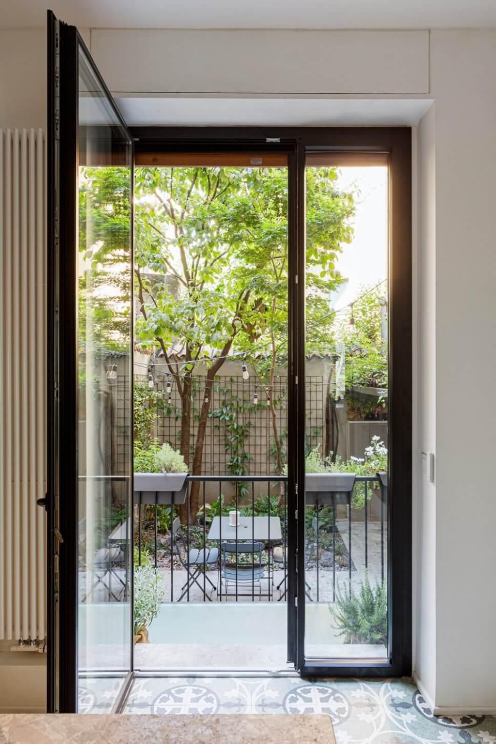 Geöffnete Balkontür mit Blick auf begrünten Innenhof mit Tisch-Stuhl-Ensemble