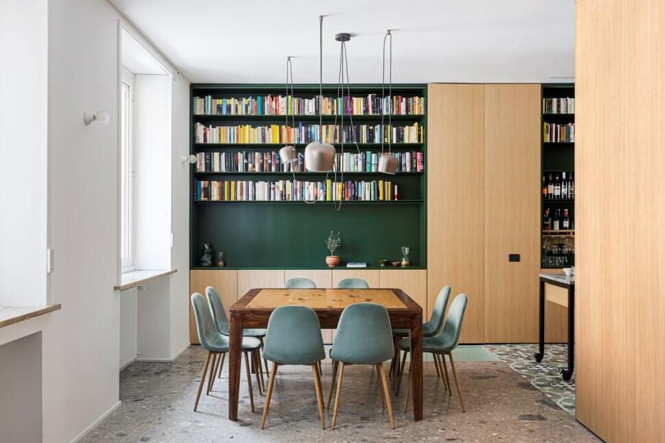 Modernes Esszimmer mit Einbauschrank aus Holz und Bücherregal auf grünem Grund mit Holztisch und acht grüngrauen Samtstühlen auf grauem Steinboden