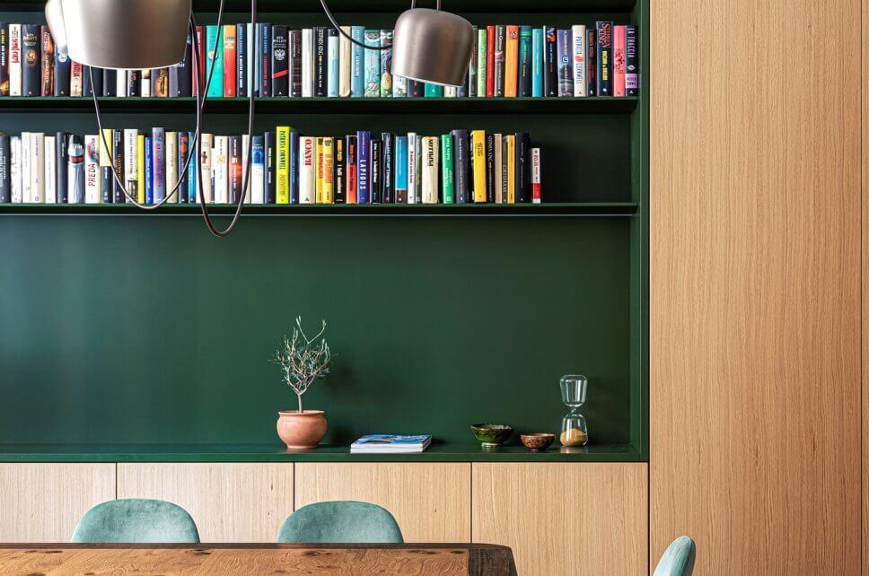 Modernes Esszimmer mit Einbauschrank aus Holz und Bücherregal auf grünem Grund mit Holztisch und grüngrauen Samtstühlen