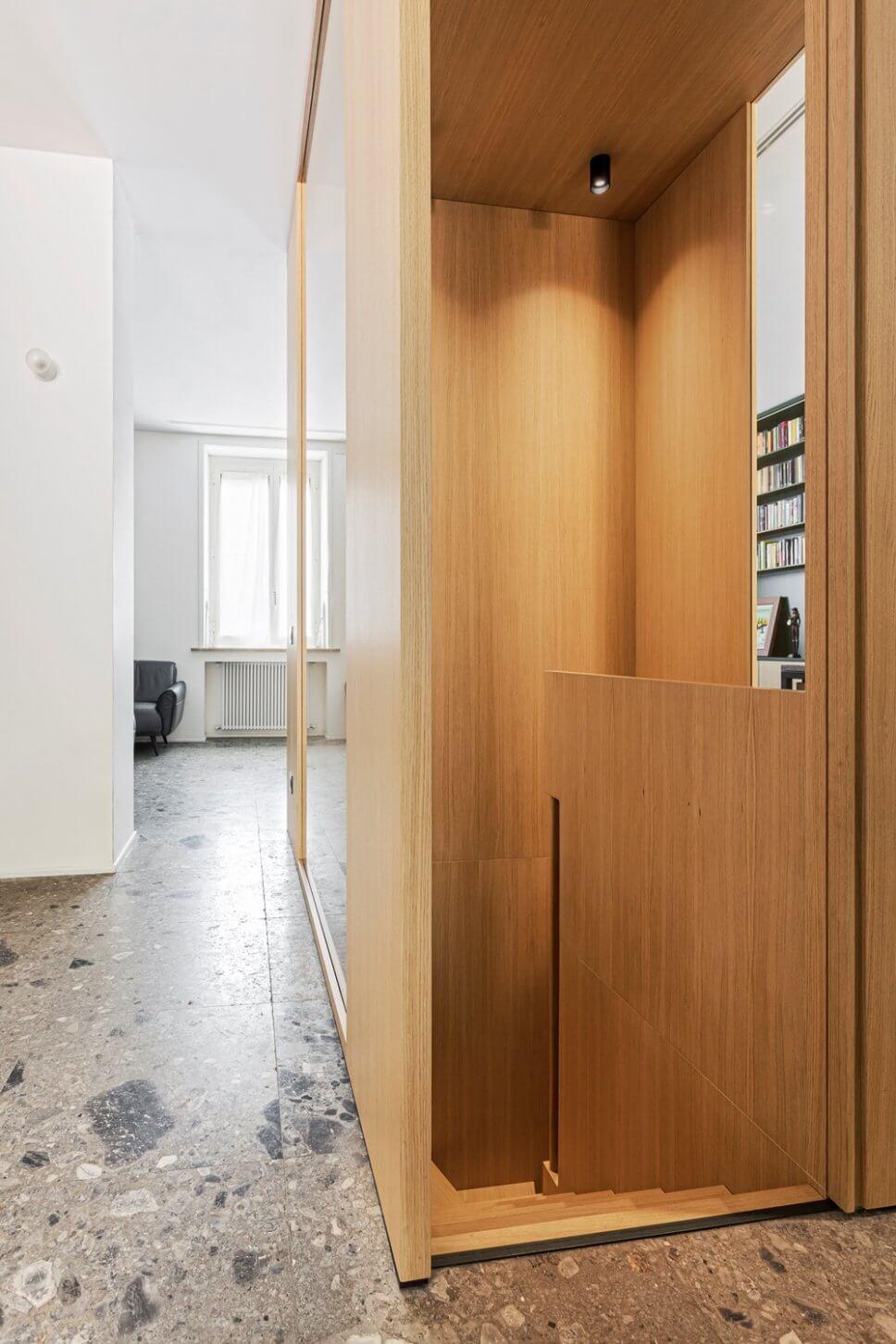 Treppenabgang aus hellem Holz mit Wandverkleidung aus gleichem Holz auf grauem Steinboden