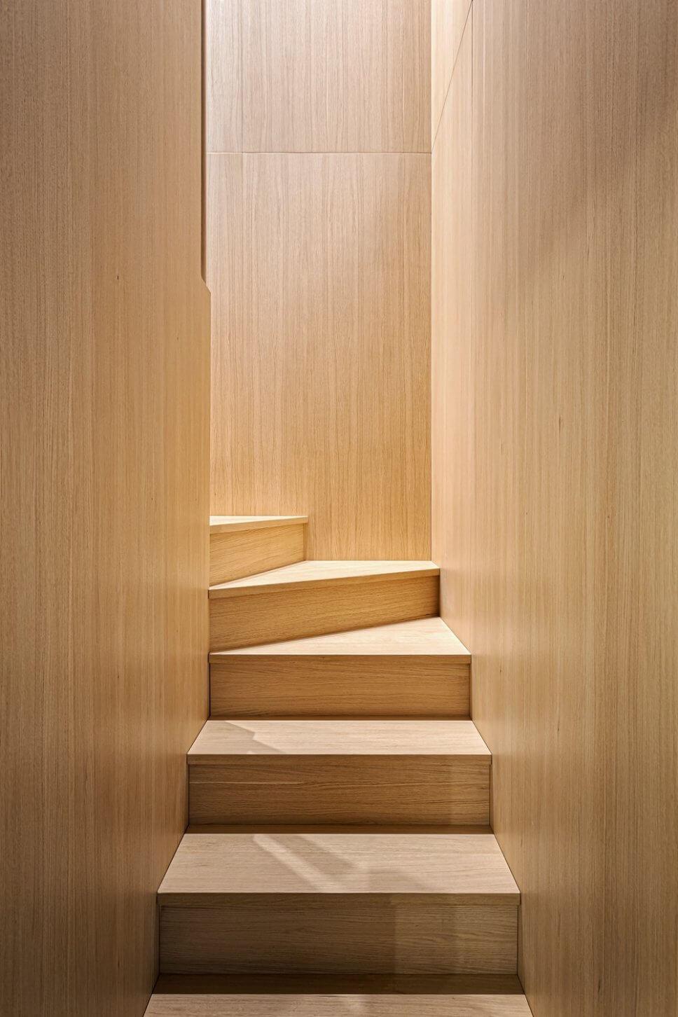 Treppe aus hellem Holz mit Wandverkleidung aus gleichem Holz