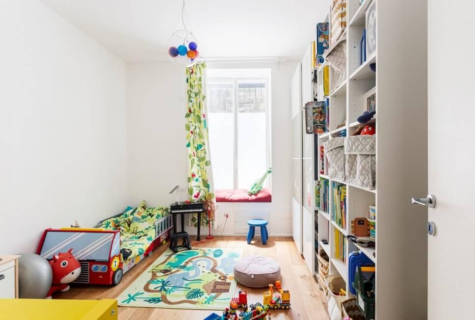 Buntes Kinderzimmer mit Bett in Form eines Feuerwehrautos, Regal, Schiebtürschrank und Spielzeug