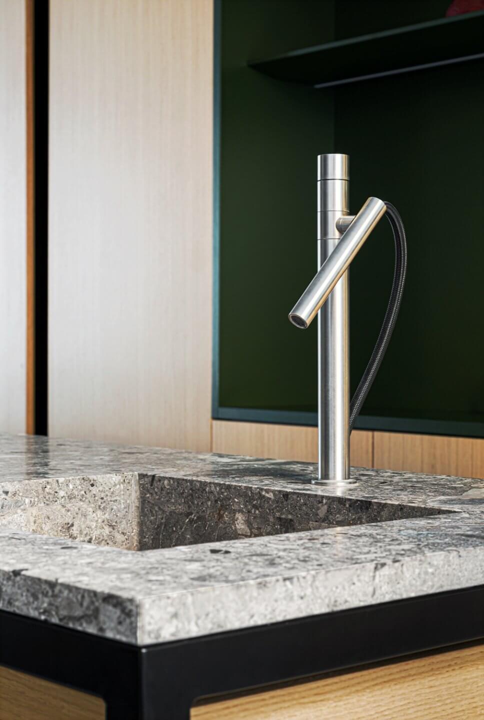 Formenreduzierter Edelstahl-Wasserhahn in moderner Wohnküche mit Marmor-Arbeitsplatte