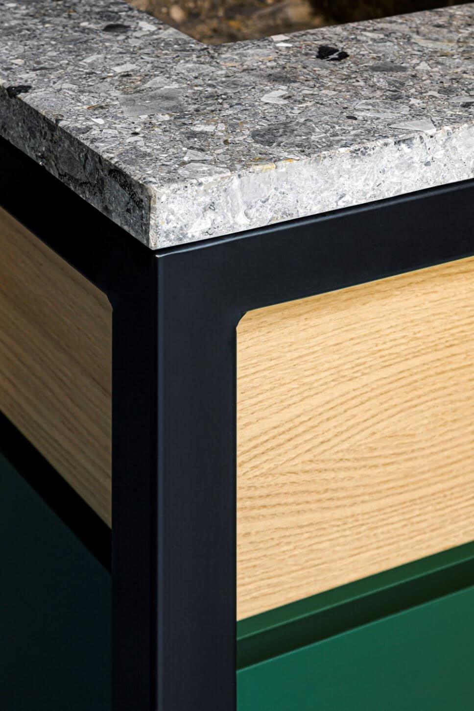 Detail einer Kücheninsel aus grauem Stein, hellem Holz und grünem Lack