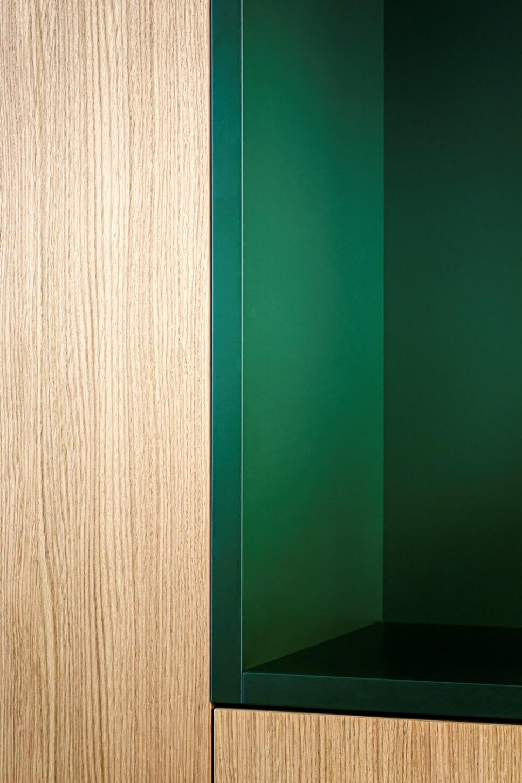 Detail einer Einbauküche aus hellem Holz und grünem Lack