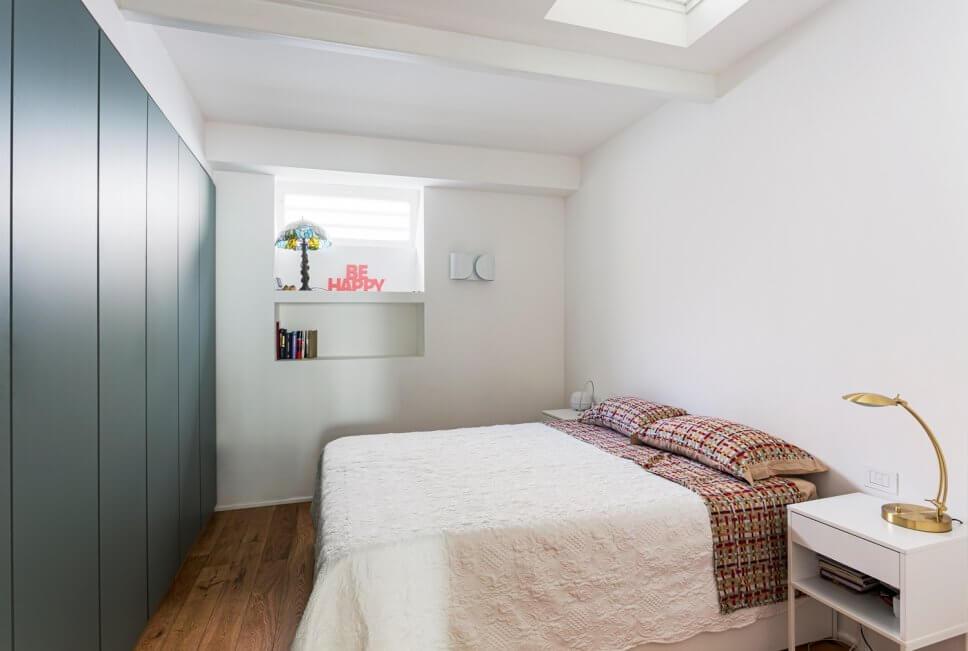Modernes Schlafzimmer mit Einbauschrank, Doppelbett und kleinem Nachttisch mit Messing-Tischleuchte