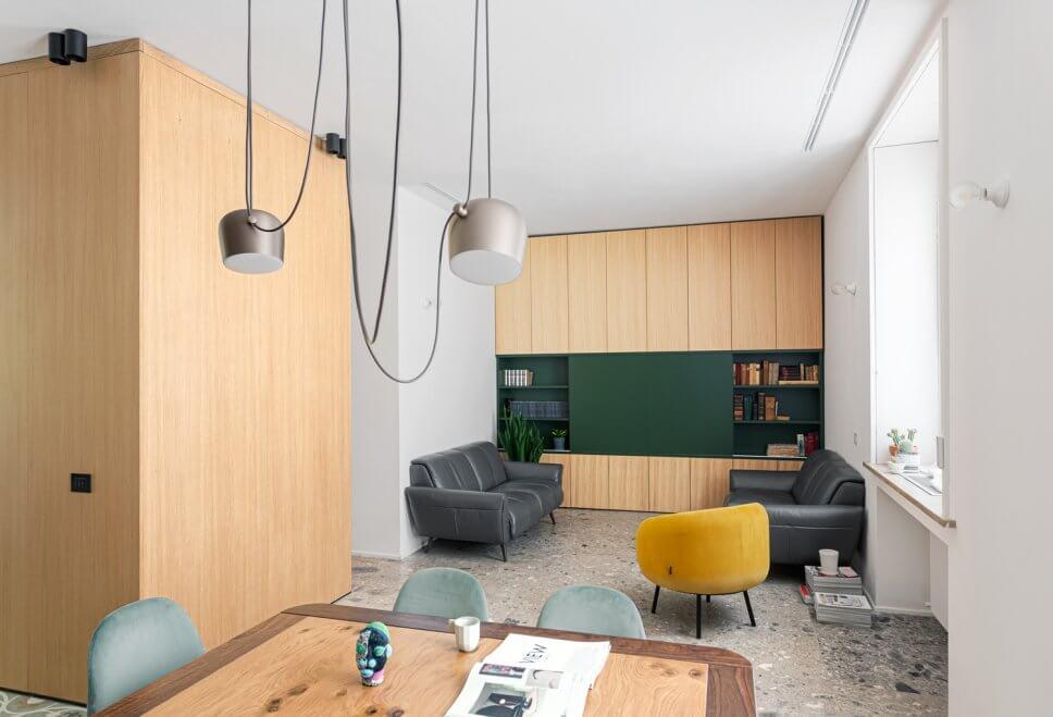 Modernes Wohnzimmer mit Einbauschrank aus Holz, zwei Ledersofas gegenüberstehend und einem gelben Samtsessel auf grauem Steinboden