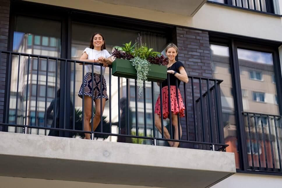 Zwei Frauen stehen neben üppig bepflanztem Balkonkasten auf Balkon