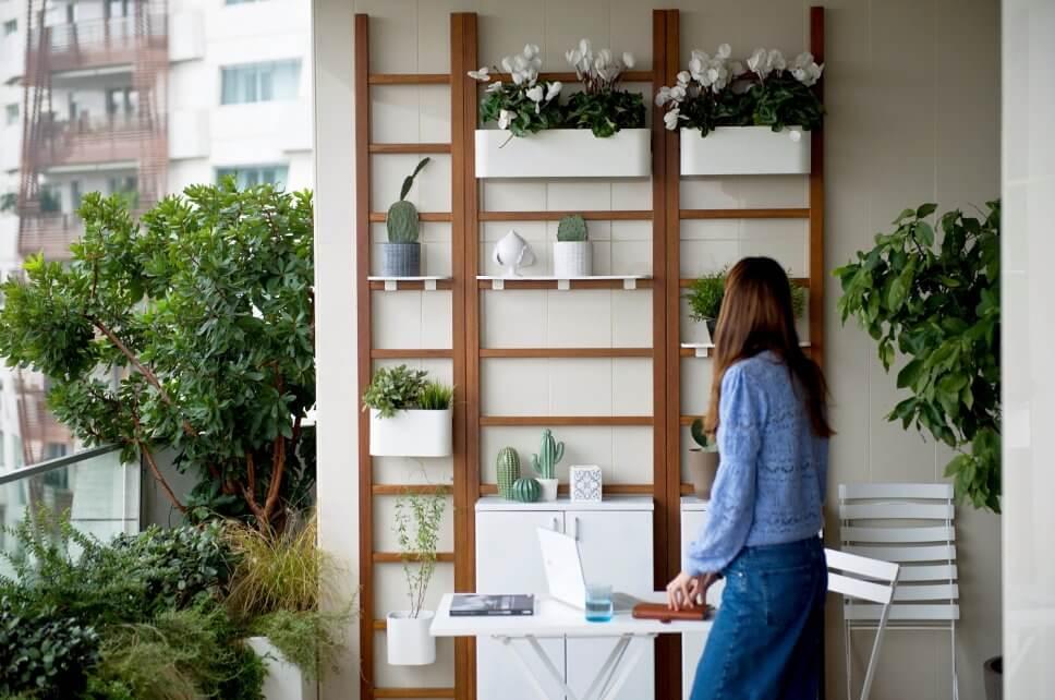 Frau steht auf einem üppig mit Kübelpflanzen und Balkonkasten bepflanzten Balkon