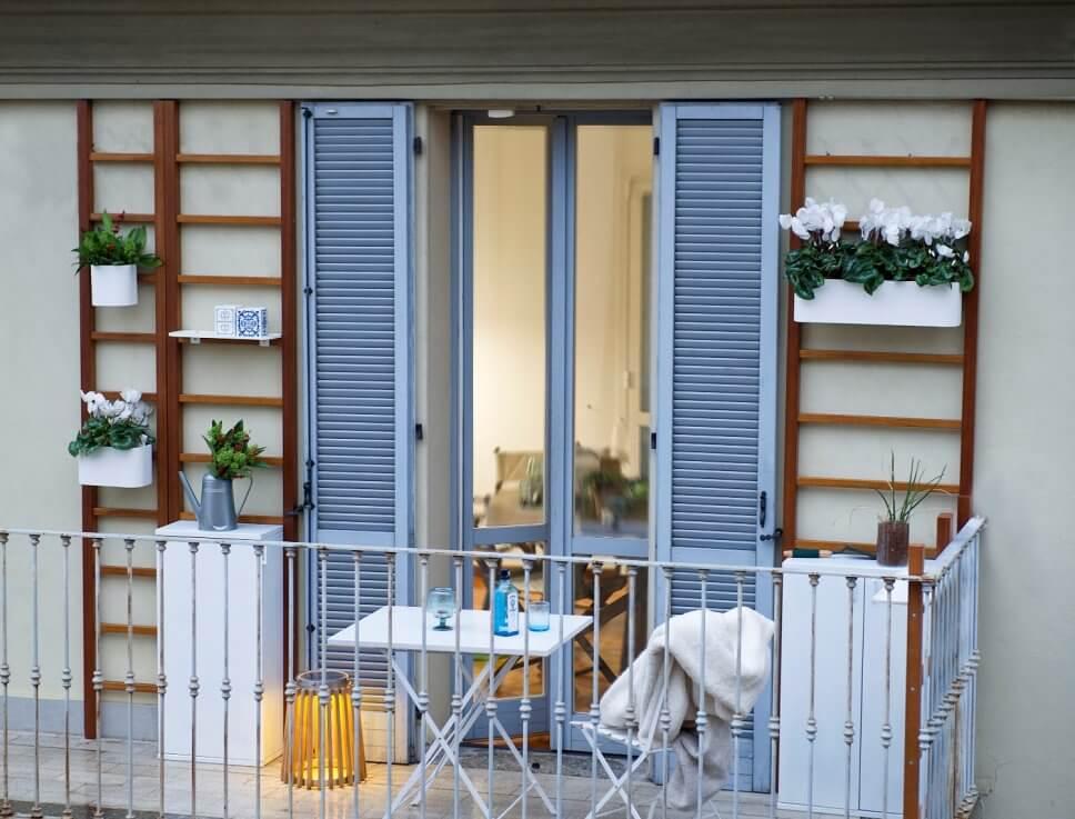 Mit Balkonkasten an Wandspalieren bepflanzter Balkon mit Klapptisch und Klappstuhl