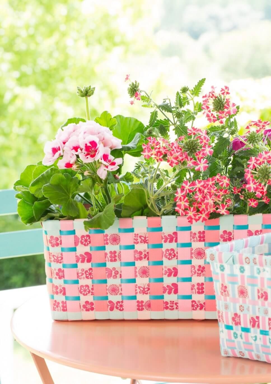 Üppig mit bunten Blumen bepflanzter Balkonkasten auf Gartentisch