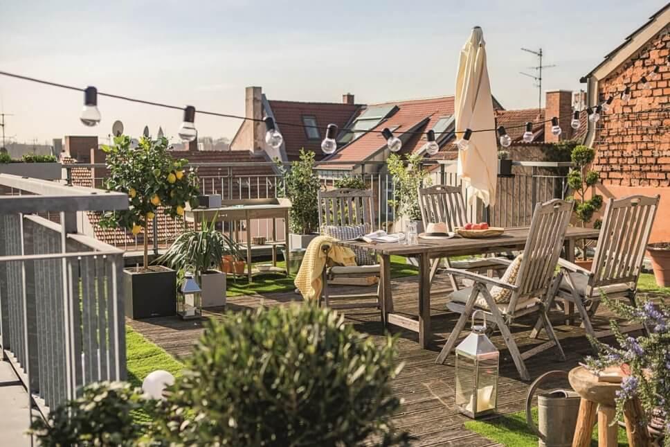 Üppig mit Kübelpflanzen und Balkonkasten bepflanzten Balkon