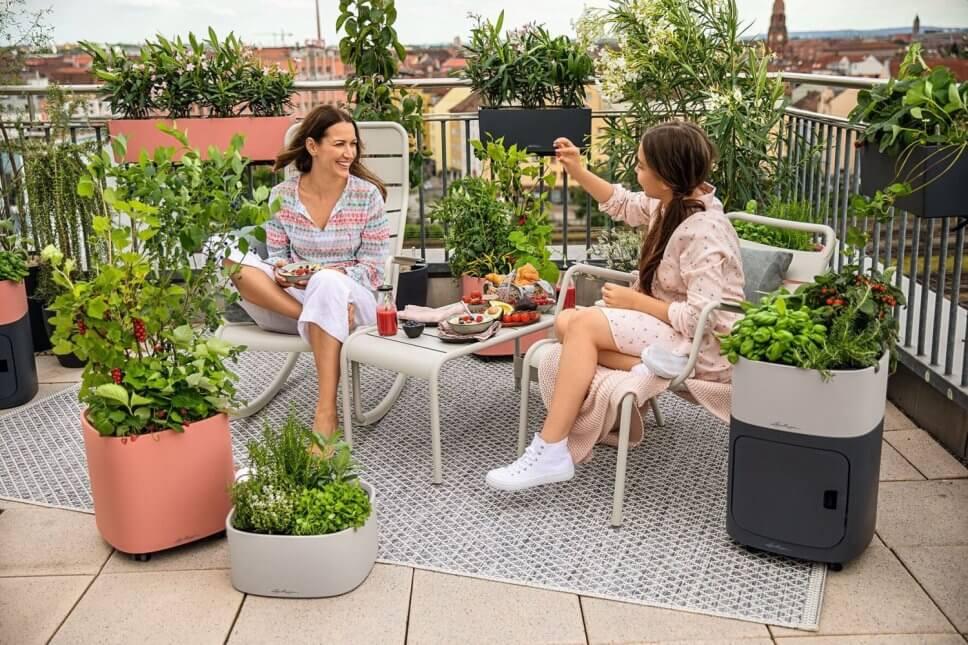 Zwei Frauen sitzen auf einem üppig mit Kübelpflanzen und Balkonkasten bepflanzten Balkon