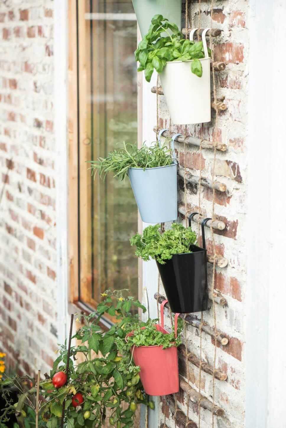 Bepflanzte Blumentöpfe übereinander gehängt an Steinwand