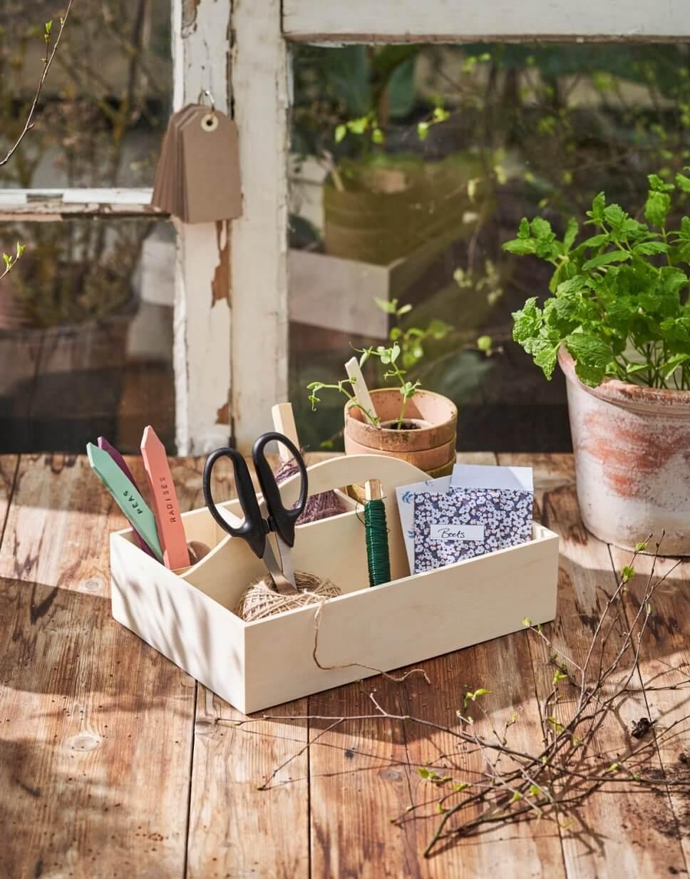 Blumentöpfe und Gartenwerkzeug auf Holztisch