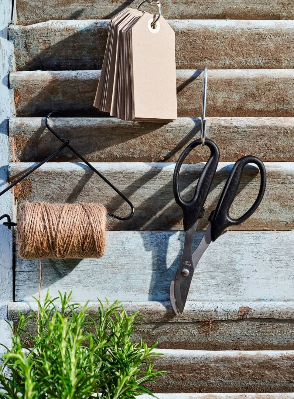 Gartenwerkzeug hängt an Haken an Holzwand
