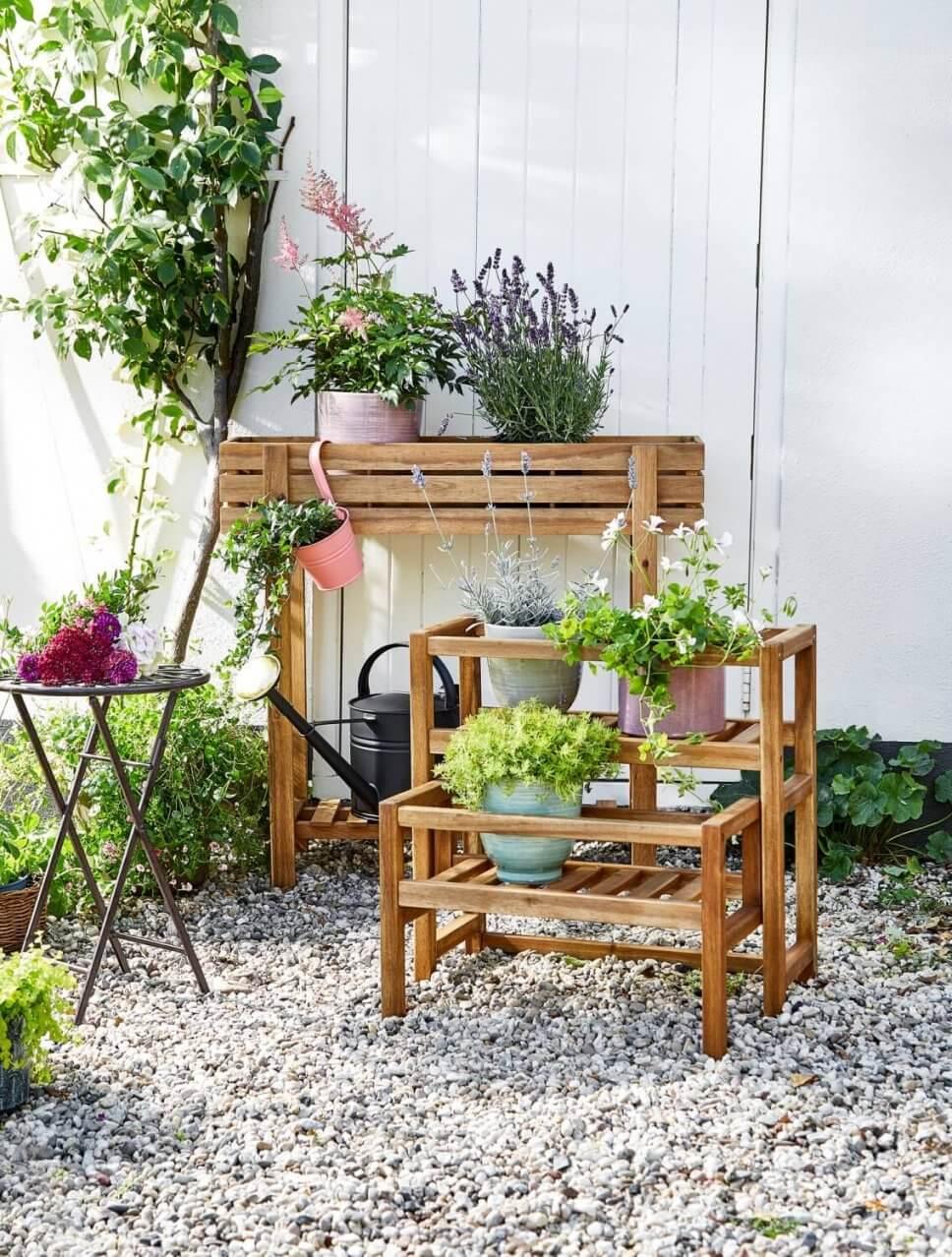 Mit Kübelpflanzen bepflanzte Blumenbänke auf Kies-Terrasse