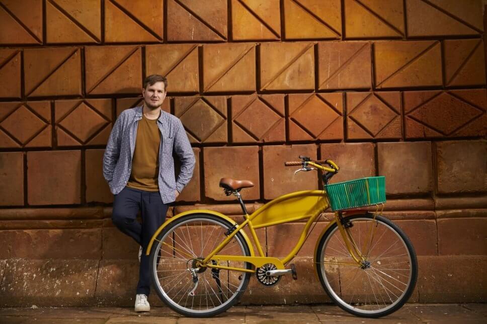 Designer Sebastian Herkner steht in Kolumbien neben einem gelben Fahrrad mit grünem Fahrradkorb