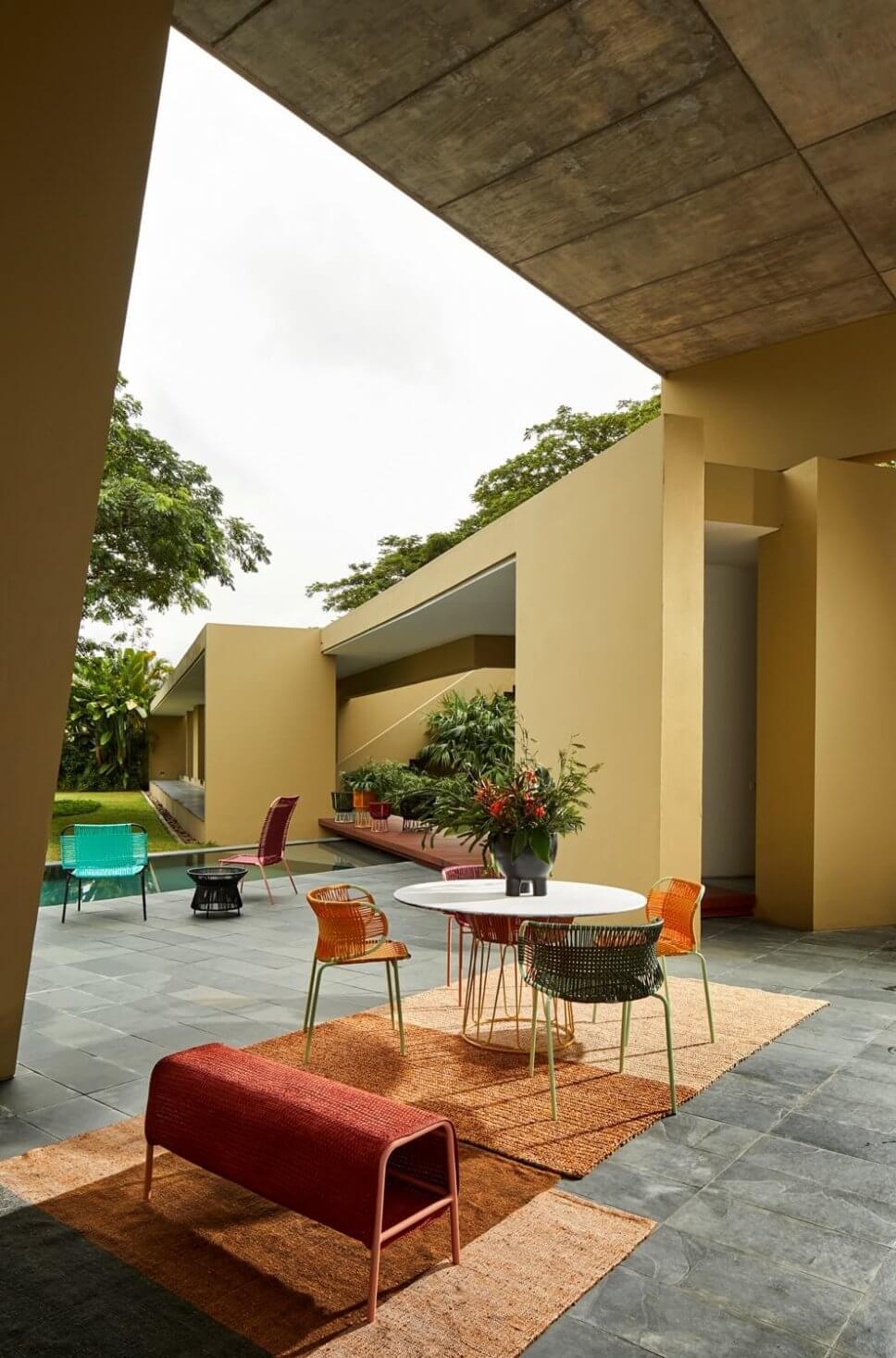 Terrasse mit Teppichen, Bank und Sesseln aus Geflecht in einer kolumbianischen Casa