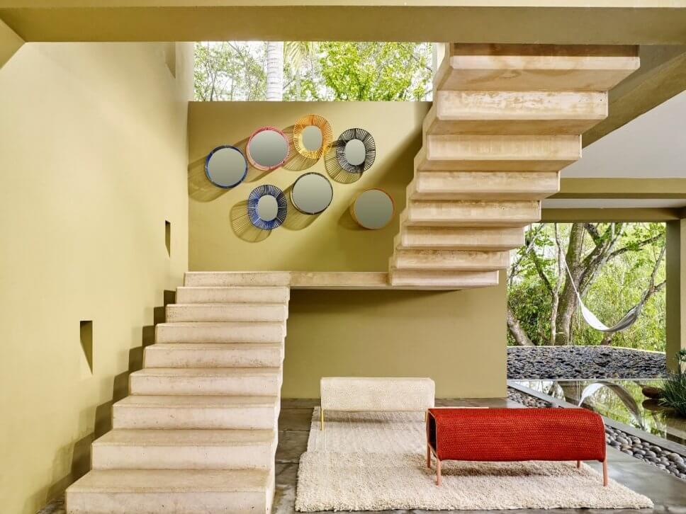Freistehende Treppe mit sieben bunt gerahmten Spiegeln an der Wand und Terrasse mit Teppich und zwei Bänken aus Geflecht in einer kolumbianischen Casa