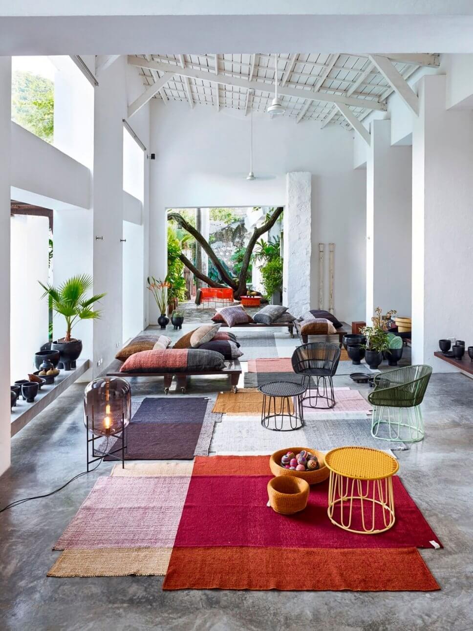 Offener Wohnraum bunten Teppichen, Kissen und mit Sesseln aus buntem Geflecht in einer kolumbianischen Casa