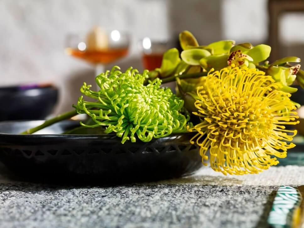 Schwarze Keramikschale mit exotischen gelben Blüten gefüllt