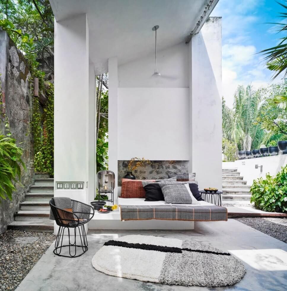 Terrasse mit Teppichen, Kissen und mit Sessel aus Geflecht in einer kolumbianischen Casa