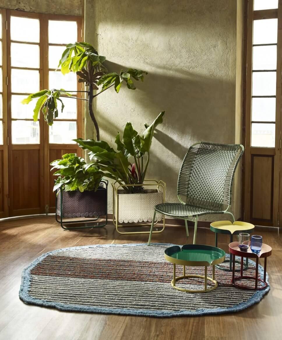 Wohnraum mit Sessel aus buntem Geflecht und einigen Coffeetable auf Teppich in einem kolumbianischen Kolonialhaus
