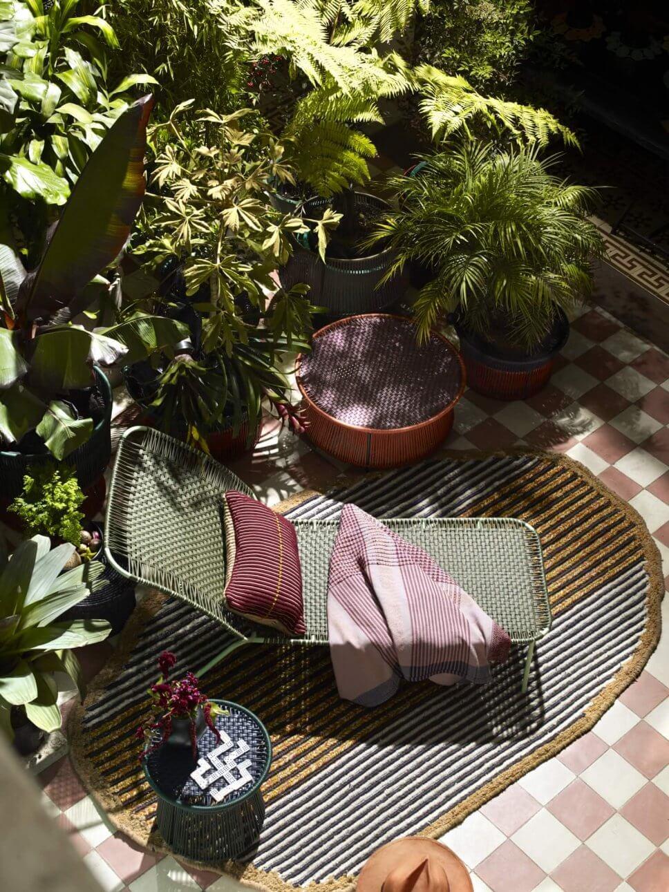 Sonnenliege auf Teppich im üppig bepflanzten Patio eines kolumbianischen Kolonialhauses