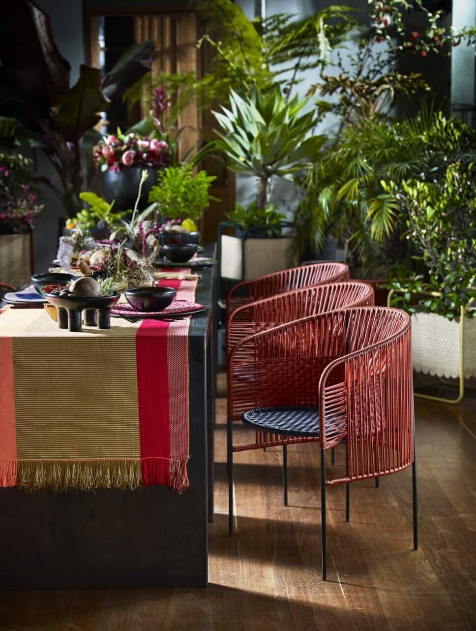 Gedeckter Tisch mit bunten Geflechtstühlen im üppig bepflanzten Raum eines kolumbianischen Kolonialhauses