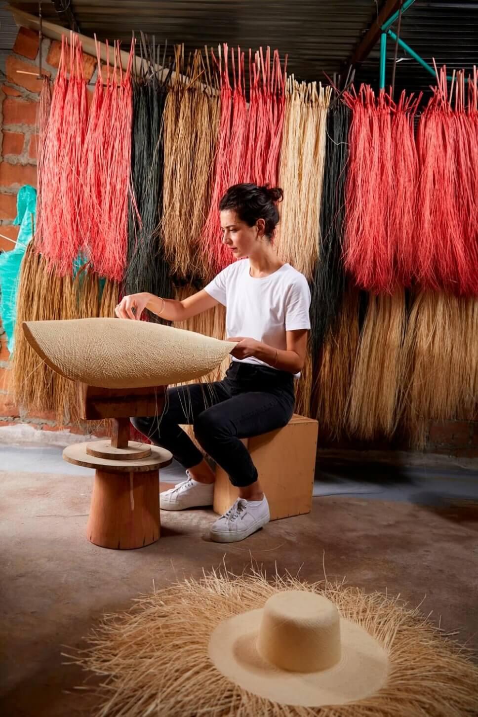 Designerin Pauline Deltour arbeitet in Kolumbien an einem Rohling eines Panama-Hutes. An der Wand hinter ihr hängen zu Bündeln gebundene Fasern der Iraca-Palme
