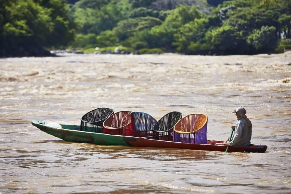 Mann fährt auf einem Ruderboot fünf Sessel aus buntem Geflecht über einen Fluss