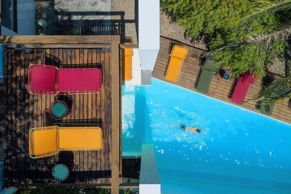 Blick aus der Vogelperspektive auf Pool und umliegenden Holzterrassen mit Sonnenliegen aus buntem Geflecht in einer kolumbianischen Casa