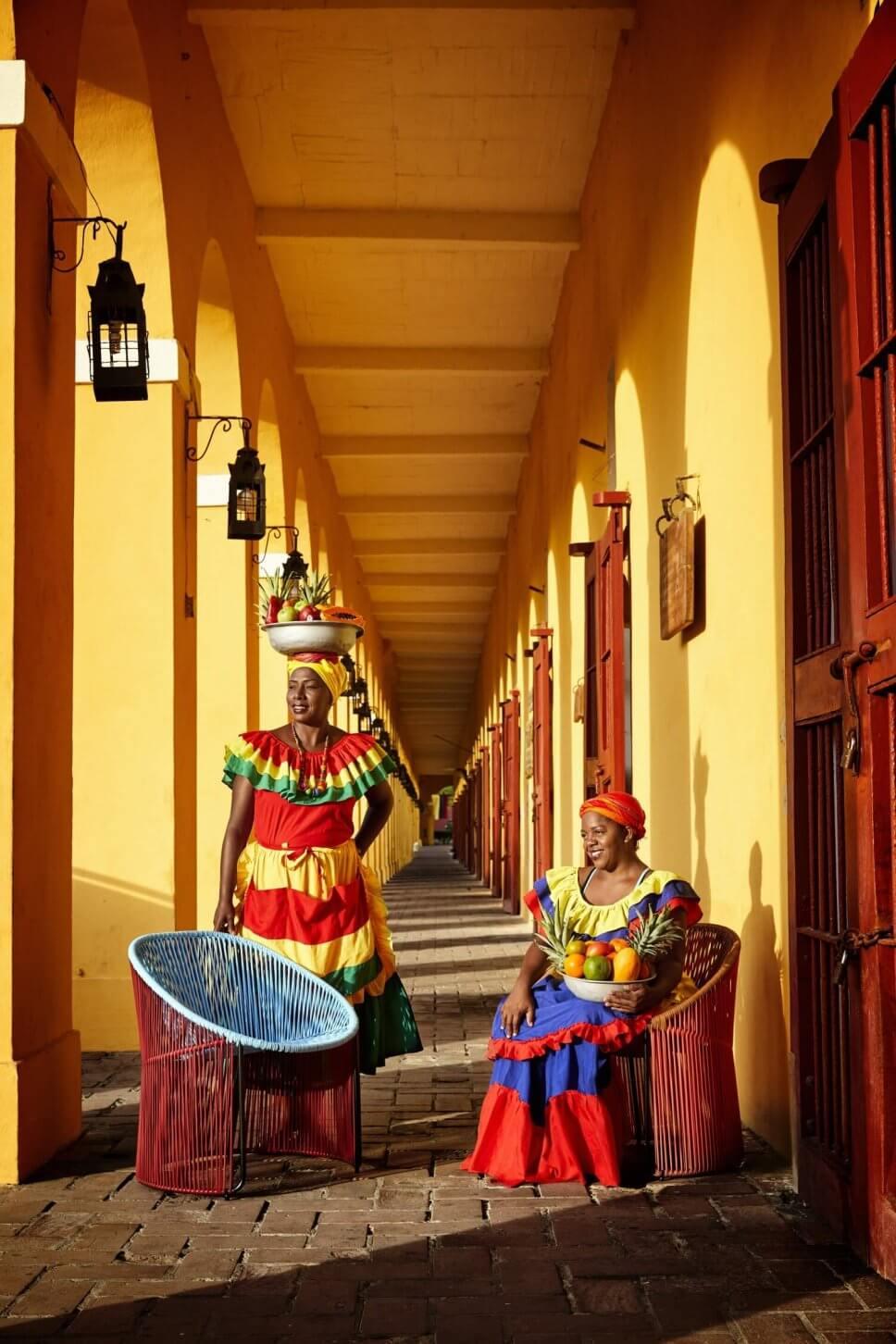 Zwei kolumbianische Frauen in farbenfrohe Tracht stehen vor zwei Sesseln aus buntem Geflecht in einem Laubengang in einer karibischen Kolonialstadt