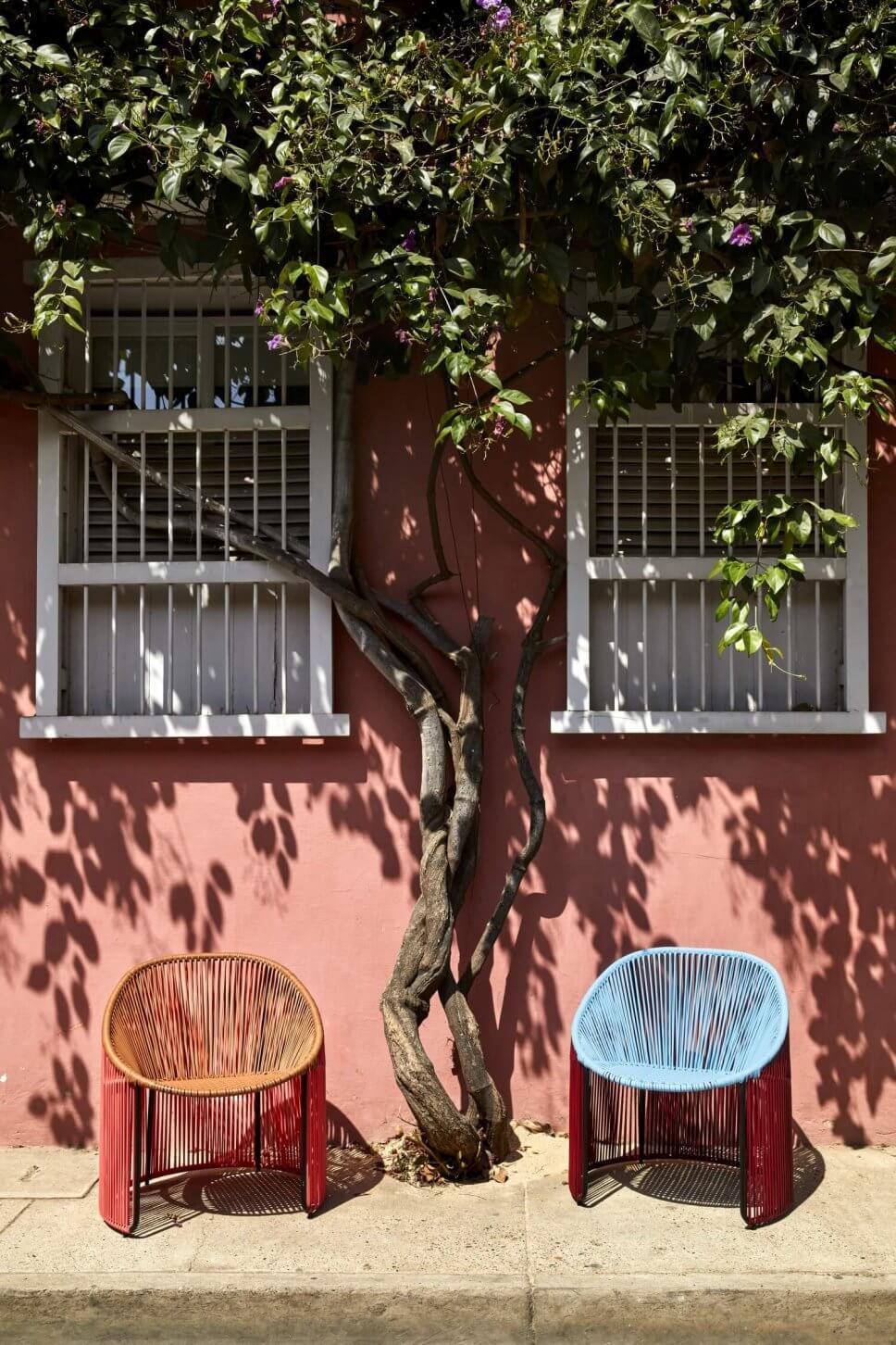 Sessel aus buntem Geflecht stehen vor Altbau in einer karibischen Kolonialstadt