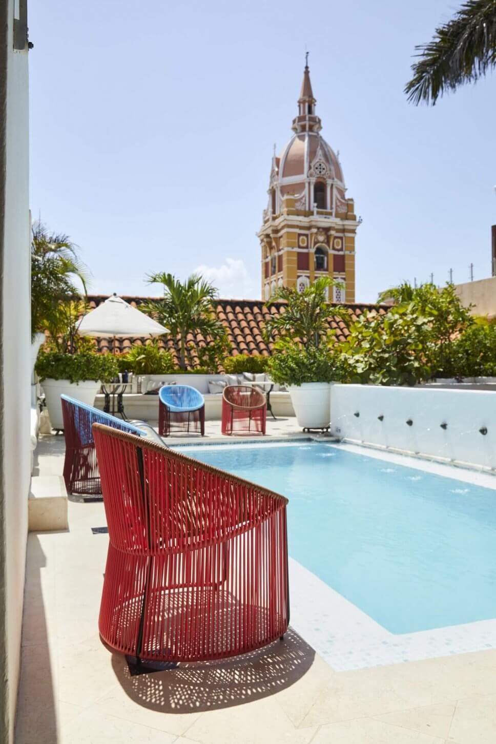 Sessel aus buntem Geflecht stehen um einem Pool in einer kolumbianischen Casa mit Blick auf Kirchturm im spanischen Kolonialstil