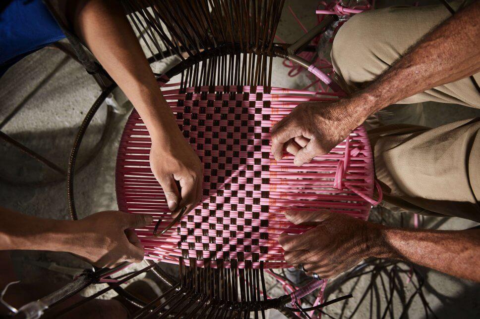 Hände flechten Sitz eines Sessel aus buntem Geflecht