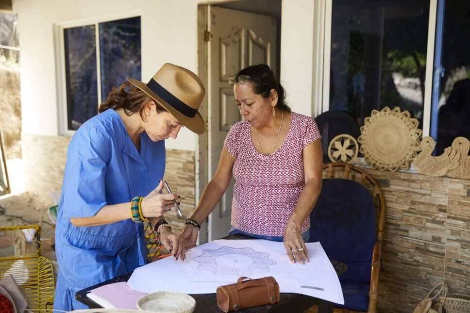 Zwei Frauen beugen sich vor einem kolumbianischen Haus über eine Zeichnung einer Wanddekoration in Sternform