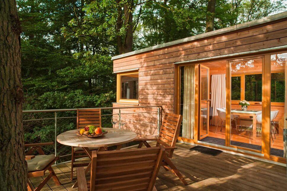 Großes Baumhaus zum Wohnen auf Stelzen im Wald mit Terrasse