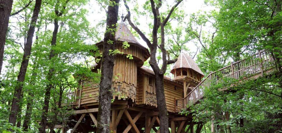 Großes Baumhaus aus Holz in Form eines Schlosses im Wald