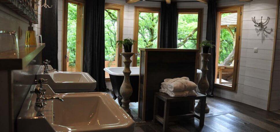 Badezimmer mit zwei Waschbecken und einer Badewanne in einem geräumigen Baumhaus