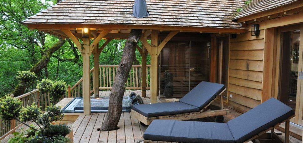 Terrasse mit Whirlpool und Sonnenliegen an einem Baumhaus