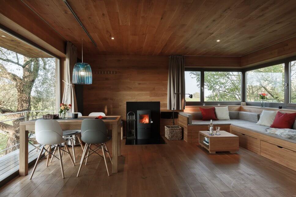 Esstisch, Kamin und Sofa in einem geräumigen Baumhaus