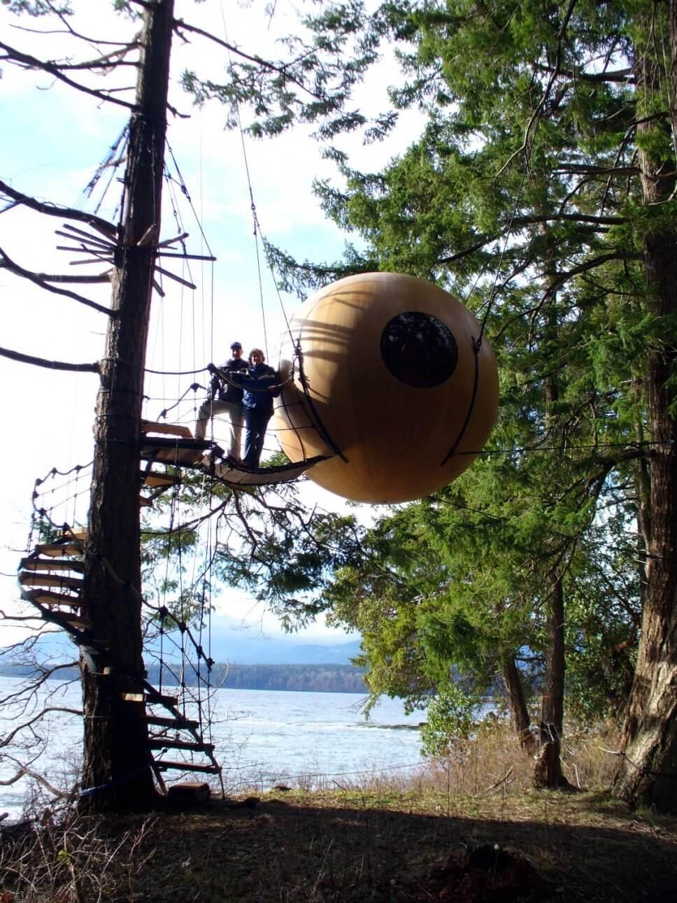 Großes Baumhaus aus Holz in Form einer hängenden Kugel im Wald