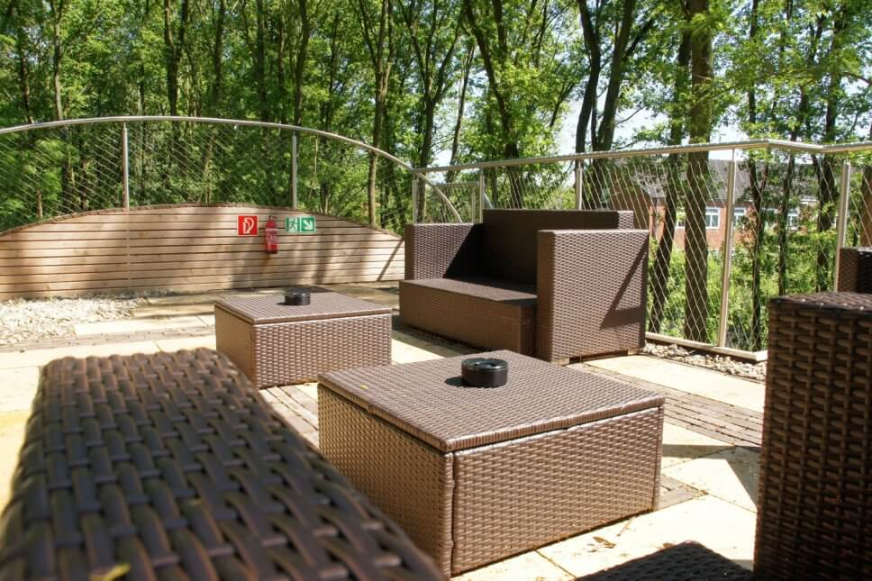 Terrasse mit Sessel und Couchtischen aus Rattan an einem Baumhaus