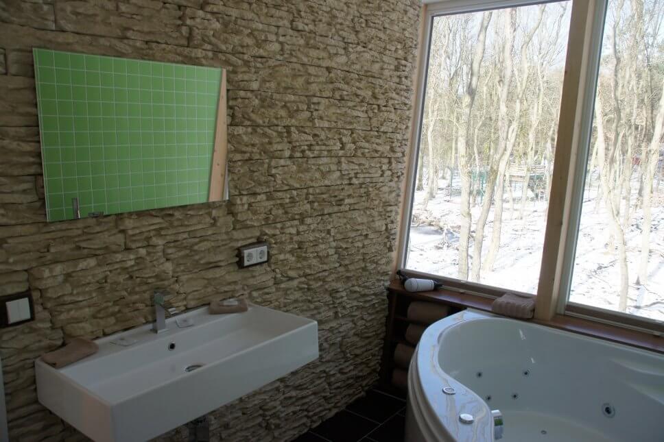 Badezimmer mit Waschbecken und einer Whirlpool-Badewanne in einem geräumigen Baumhaus
