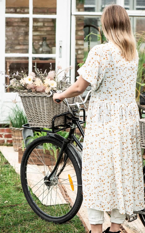 Frau im Blümchenkleid schiebt ein Fahrrad mit Blumen gefülltem Fahrradkorb vor Gewächshaus