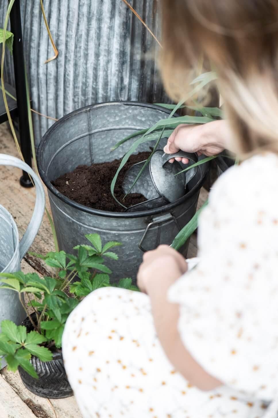 Frau gräbt mit Metallschaufel in einem Blumentopf aus Metall